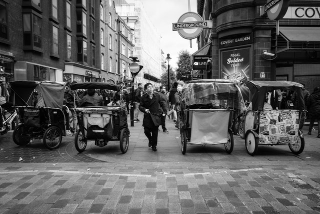 A person crossing the street among pedicabs in Covent Garden.