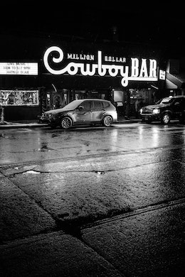 The sign of the Million Dollar Cowboy Bar lit up at night in Jackson, with its lights reflected off the wet pavement.
