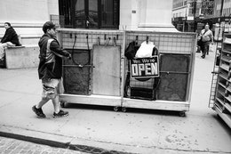 "A street vendor pushing a merchandise cart with a sign that reads ""yes, we're open"" on Wall Street."