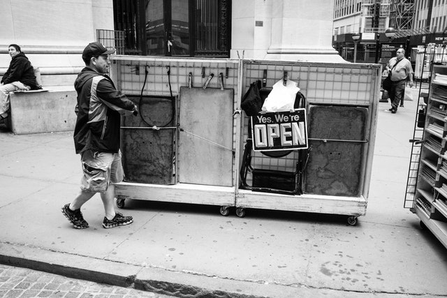 """A street vendor pushing a merchandise cart with a sign that reads """"yes, we're open"""" on Wall Street."""