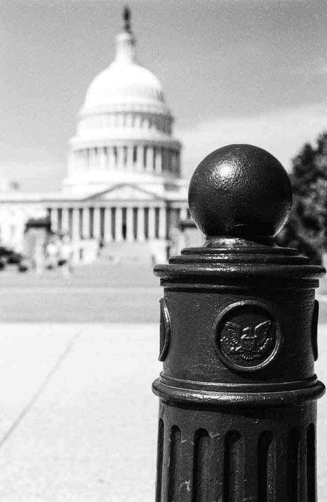 A pole bearing the seal of the United States Capitol, near the Capitol building.