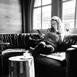Kate, enjoying some cold brew while looking at her phone at Storyville Coffee Company in Seattle.