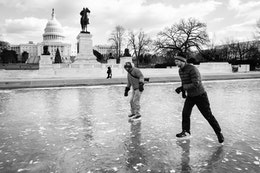 Two people ice skating on the frozen Capitol Reflecting Pool, in front of the Ulysses S. Grant Memorial and the United States Capitol.