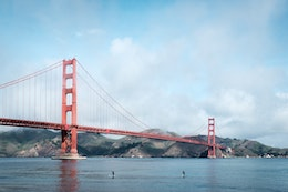 The Golden Gate Bridge, with two surfers paddling in front of it.