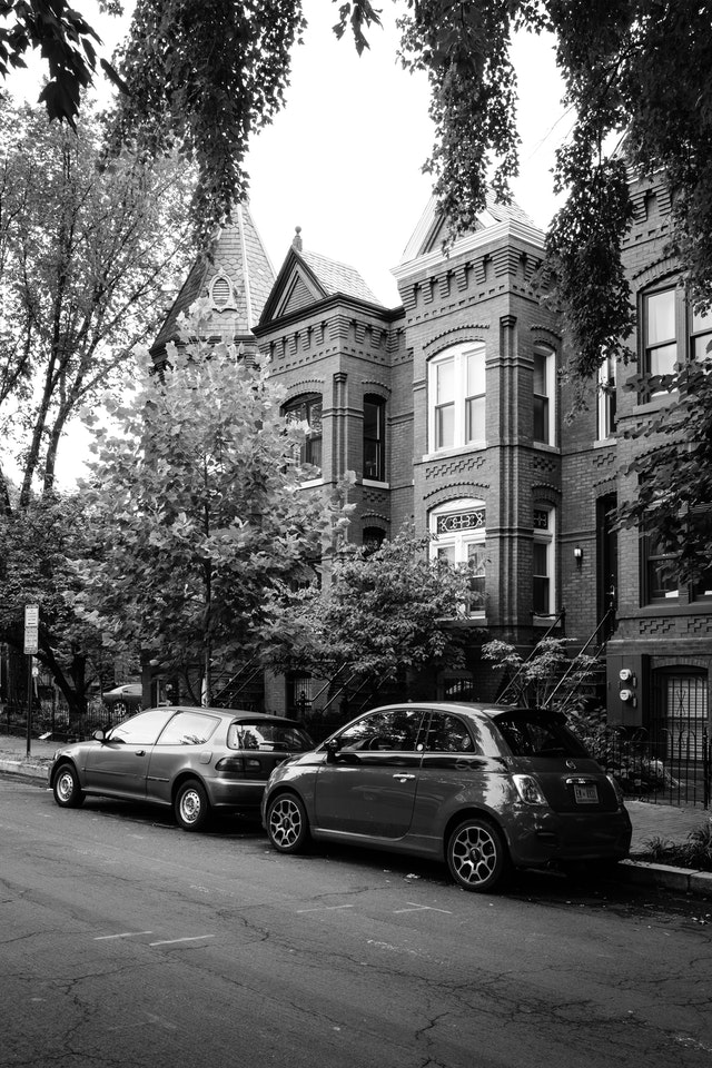 Two cars parked in front of row houses in Capitol Hill.