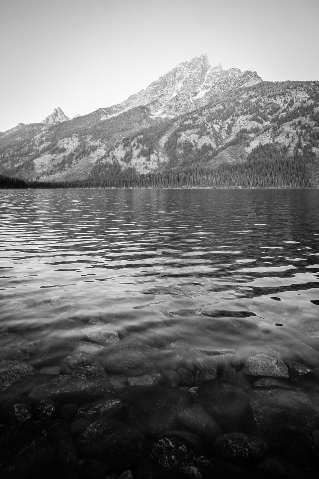 Teewinot Mountain seen from the shore of Jenny Lake. In the foreground, rocks under the surface of the lake.