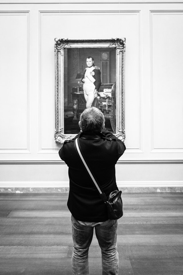 A man taking a photo of a portrait of Napoleon at the National Gallery of Art.