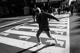 A dude making a gesture while crossing H street in Chinatown.