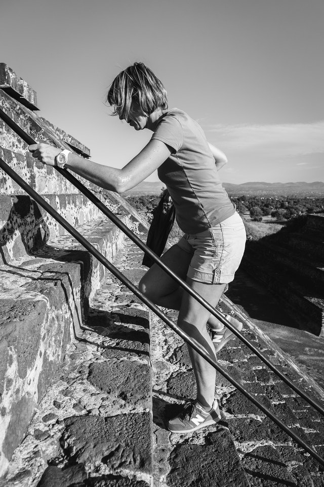 A woman climbing up the steps of the Pyramid of the Moon in Teotihuacán.