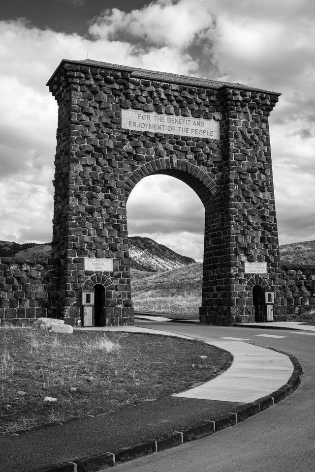 """The Roosevelt Arch at Yellowstone National Park on a sunny afternoon. The inscription at the top reads """"for the benefit and enjoyment of the people""""."""