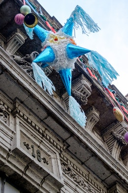 A piñata hanging from an old building in the historic center of Mexico City.