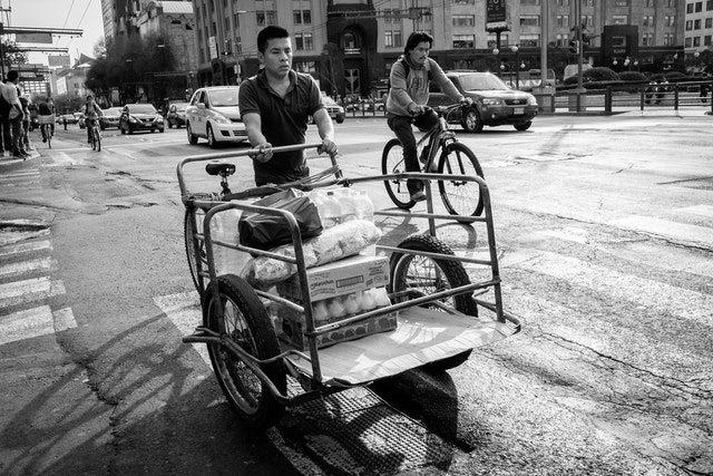 A man pushing a cart in the historic center of Mexico City.