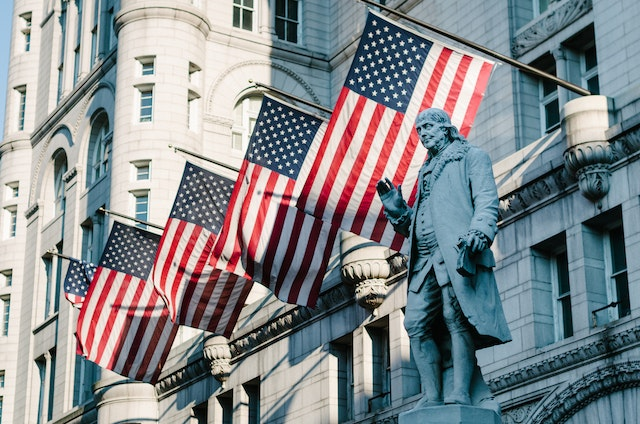 Statue of Benjamin Franklin at the Old Post Office building in Washington, DC, in front of several flags of the United States.
