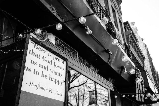 "A sign that reads ""Beer is proof that God loves us and wants us to be happy"", credited to Benjamin Franklin."
