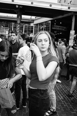 A young woman eating some kind of sandwich on the street near Pike Place Market.