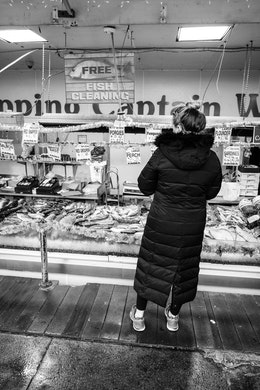 A woman shopping at Captain White's, at the Maine Avenue Fish Market.