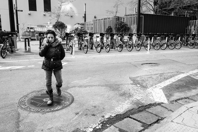 A woman crossing the street while talking on the phone, in front of a row of Citibikes.
