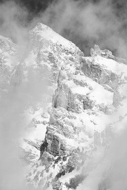 A close-up of one of the peaks of the Teton range, surrounded by clouds.