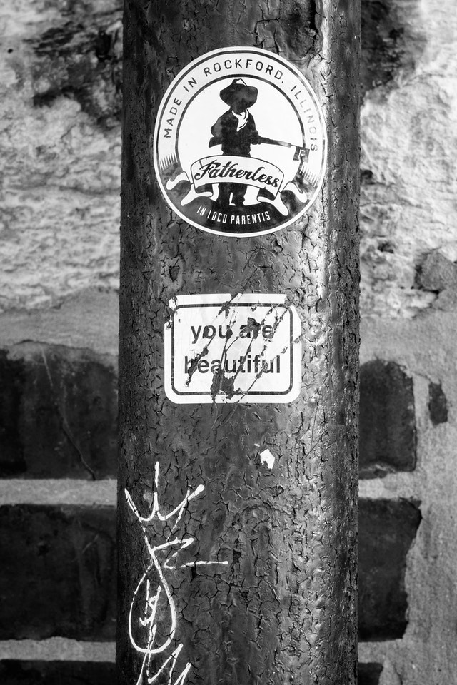 """A sticker on a pipe, that says """"you are beautiful""""."""
