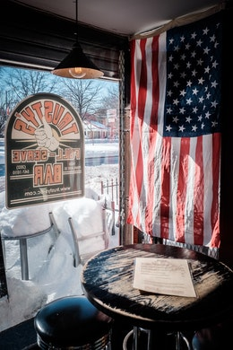 A table inside Trusty's, next to the window, with the American flag hanging from the wall.