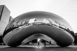 Cloud Gate at Millennium Park in Chicago, from the side, with buildings reflected off of it.