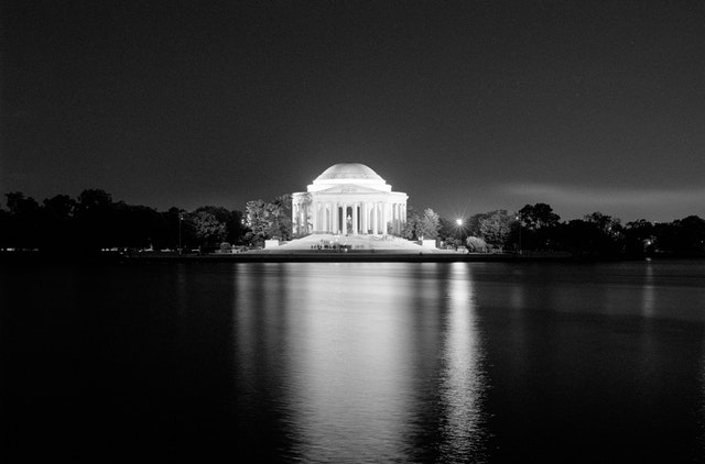 The Jefferson Memorial reflected off the Tidal Basin at night.