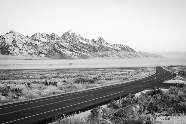 The Tetons, blanketed in fog at sunrise, with the main park road in the foreground.