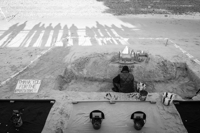 A street artist building a sand castle on the banks of the river Thames.