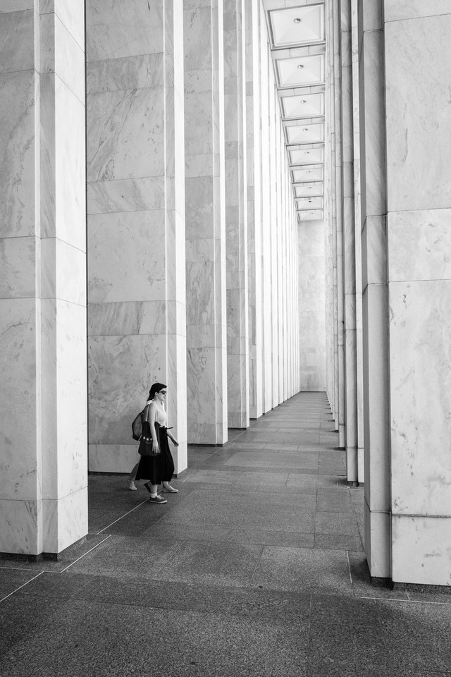 Two people walking past the columns of the Madison building of the Library of Congress.