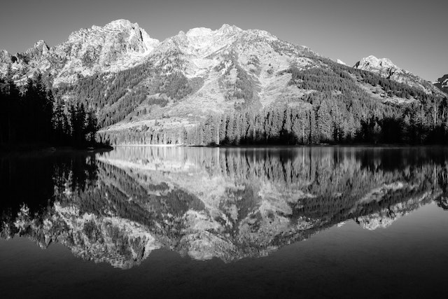 The Tetons reflected in the waters of String Lake. From left to right, Symmetry Spire, Mount Saint John, and Rockchuck Peak.