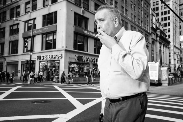 A man smoking a cigarette while crossing Broadway in New York's Financial District.