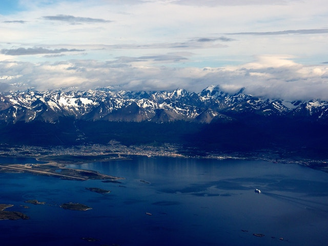 View of Ushuaia, with snow-covered mountains in the background, and an approaching cruise ship in the foreground, from the plane, before a quick layover.