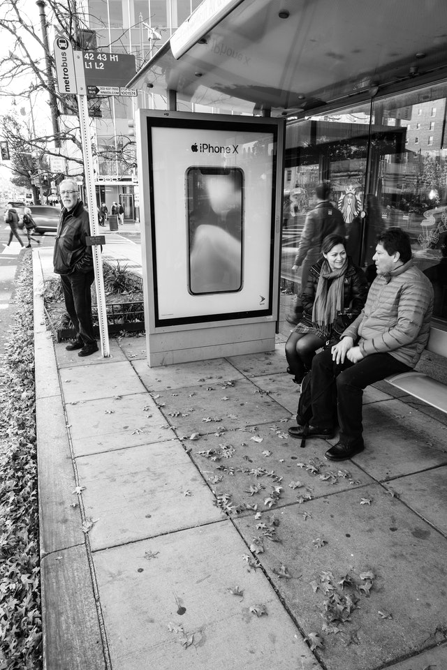 People sitting at a bus stop on Connecticut Avenue NW.