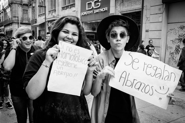 "Two people holding signs on the street in Mexico City, which read ""si no es homofóbico regáleme un abrazo"" (if you're not homophobic, give me a hug) and ""se regalan abrazos"" (free hugs)."
