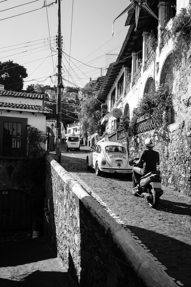 Traffic driving uphill on a street in Taxco.