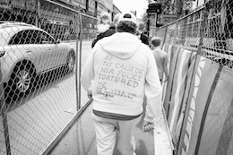 """A man walking down Market Street wearing a white hoodie with """"the California police tortured me / don't vote for the incumbents please"""" written in sharpie."""