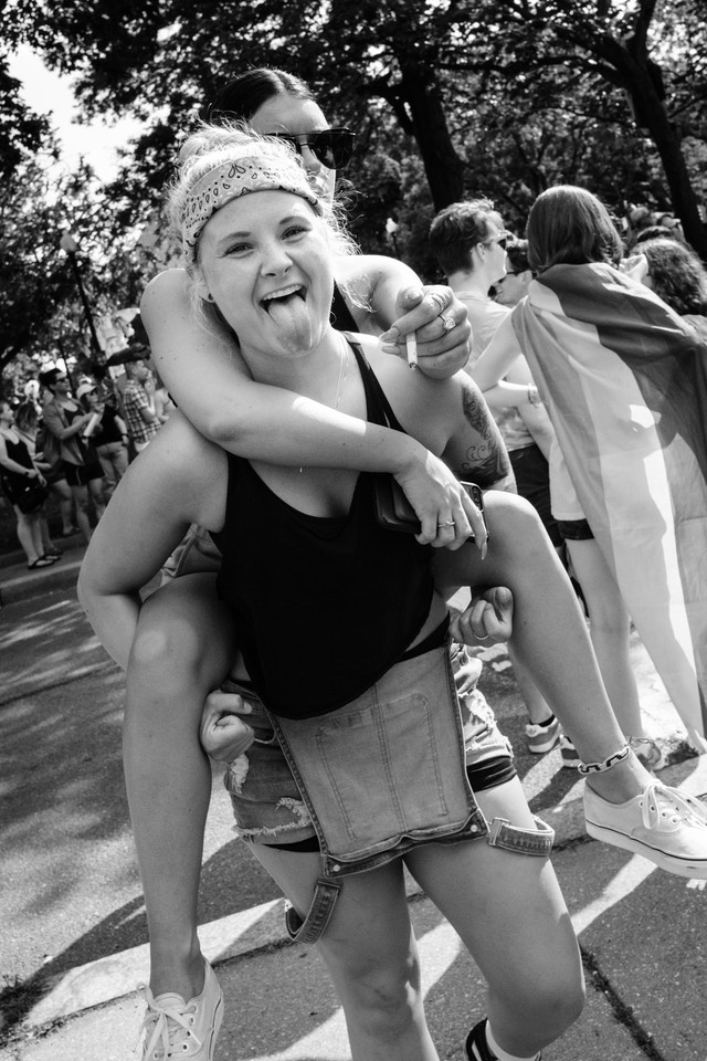 A person sticking out their tongue while carrying another person on piggyback at the Capital Pride Parade.