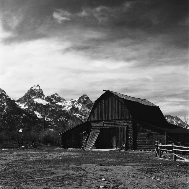The 4 Lazy F barn, with Grand Teton, Mount Owen, and Teewinot Mountain in the background.