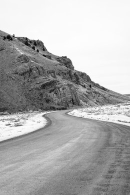 A winding road at the National Elk Refuge, leading past Millers Butte.