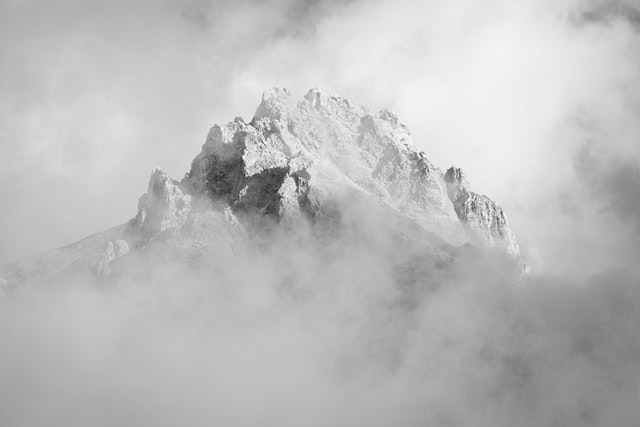 The summit of Teewinot Mountain seen among clouds.