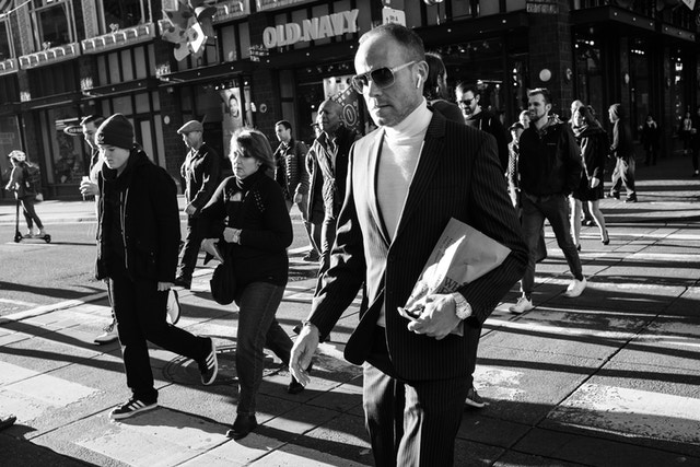 A man wearing a pinstripe suit, a turtleneck, and sunglasses, crossing the street with other pedestrians near Market Street.