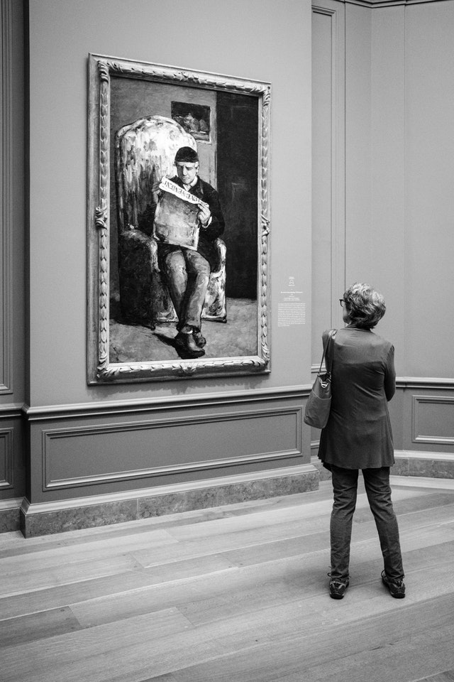 """A person examining Cézanne's """"The Artist's Father"""", at the National Gallery of Art."""
