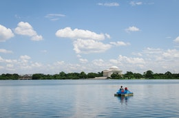 A paddleboat in the Tidal Basin with the Jefferson Memorial in the background, in Washington, DC.