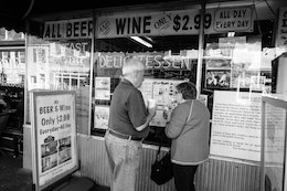 Two people looking at the menu of Chick & Ruth's Delly in Annapolis, Maryland.
