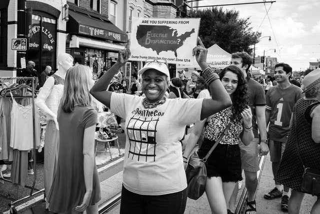 """A woman holding up a sign that reads """"are you suffering from electile dysfunction?"""". She's also wearing a """"Don the Con"""" t-shirt."""