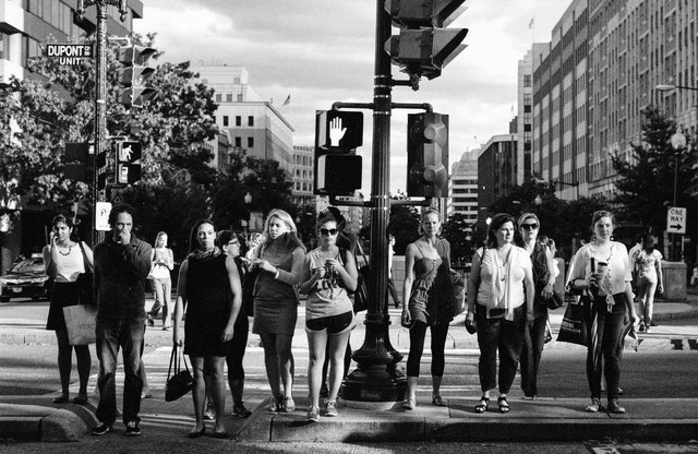 A group of pedestrians waiting to cross the street in Dupont Circle, Washington, DC.