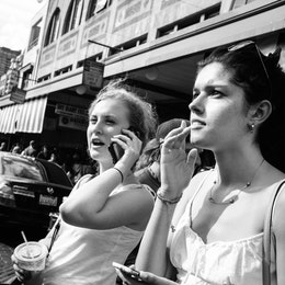 Two women standing while holding their phones at Pike Place Market.