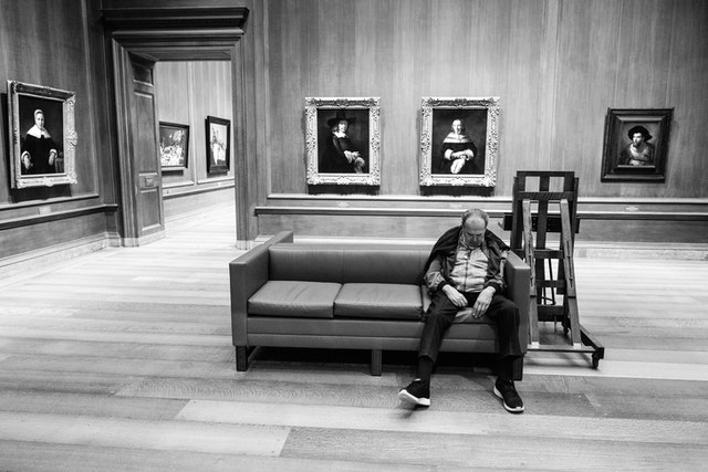 A man asleep on a couch at the National Gallery of Art.