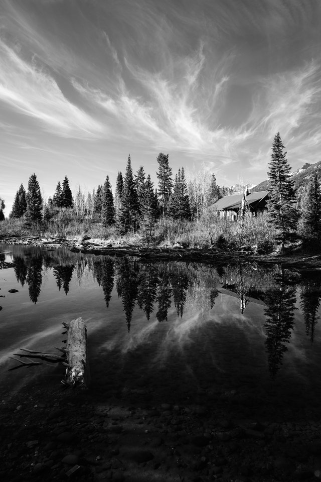 Trees, clouds and a private residence reflected off the waters of Jenny Lake at Grand Teton National Park.