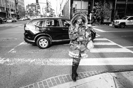 A woman wearing a camo coat crossing the street near CityCenterDC while talking on the phone.